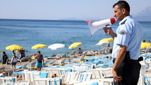 Polis elinde megafonla sahile indi