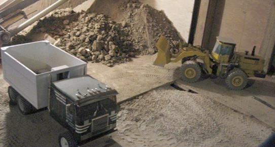 Bodrumunda oyuncak kamyonlarla inşaat yapıyor