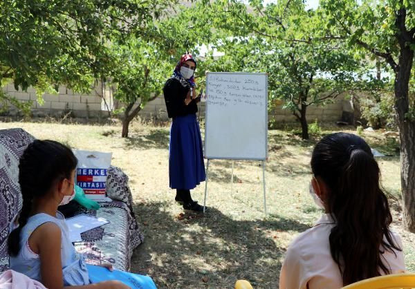 Gamze öğretmen, elinde tahtasıyla kapı kapı dolaşıp ders anlatıyor